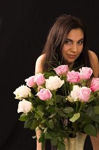 Girl smiling behind flowers